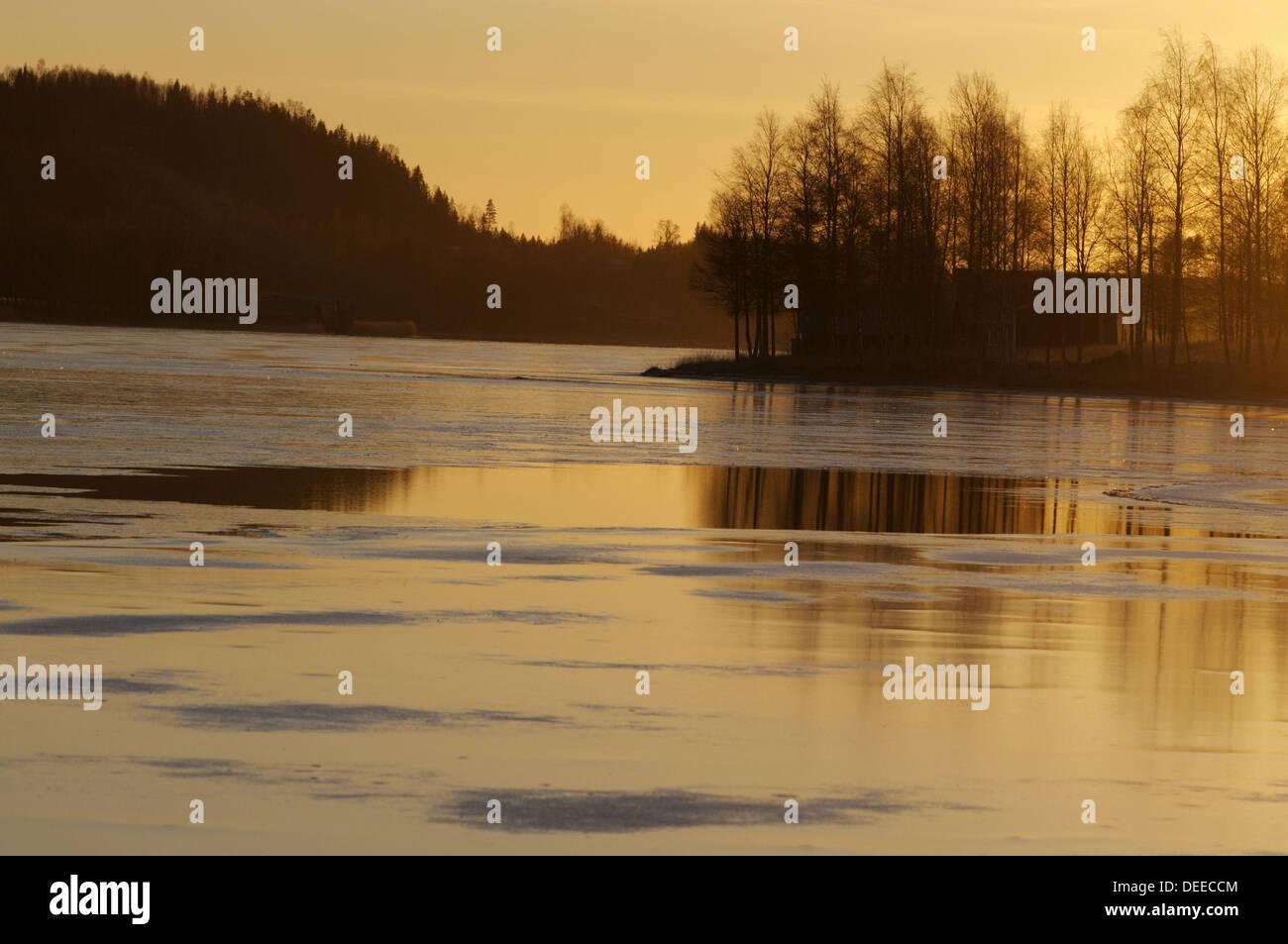 The sky at sunset is refected on thin ice on a lake near Nordingrå. High Coast / Höga Kusten, Västernorrland, Norrland, Sweden, - Stock Image