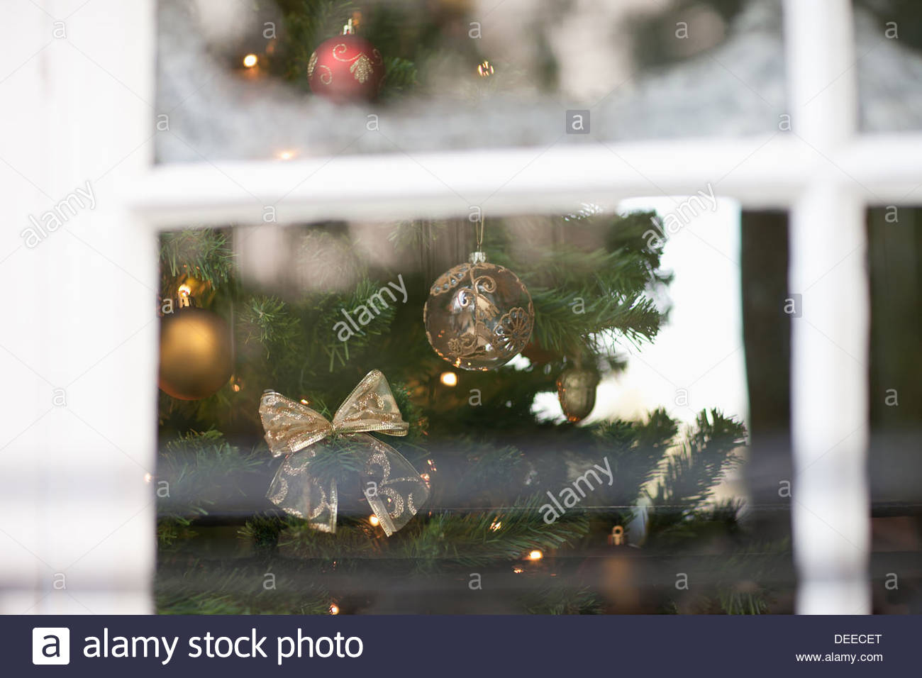 Christmas ornaments on tree behind window - Stock Image