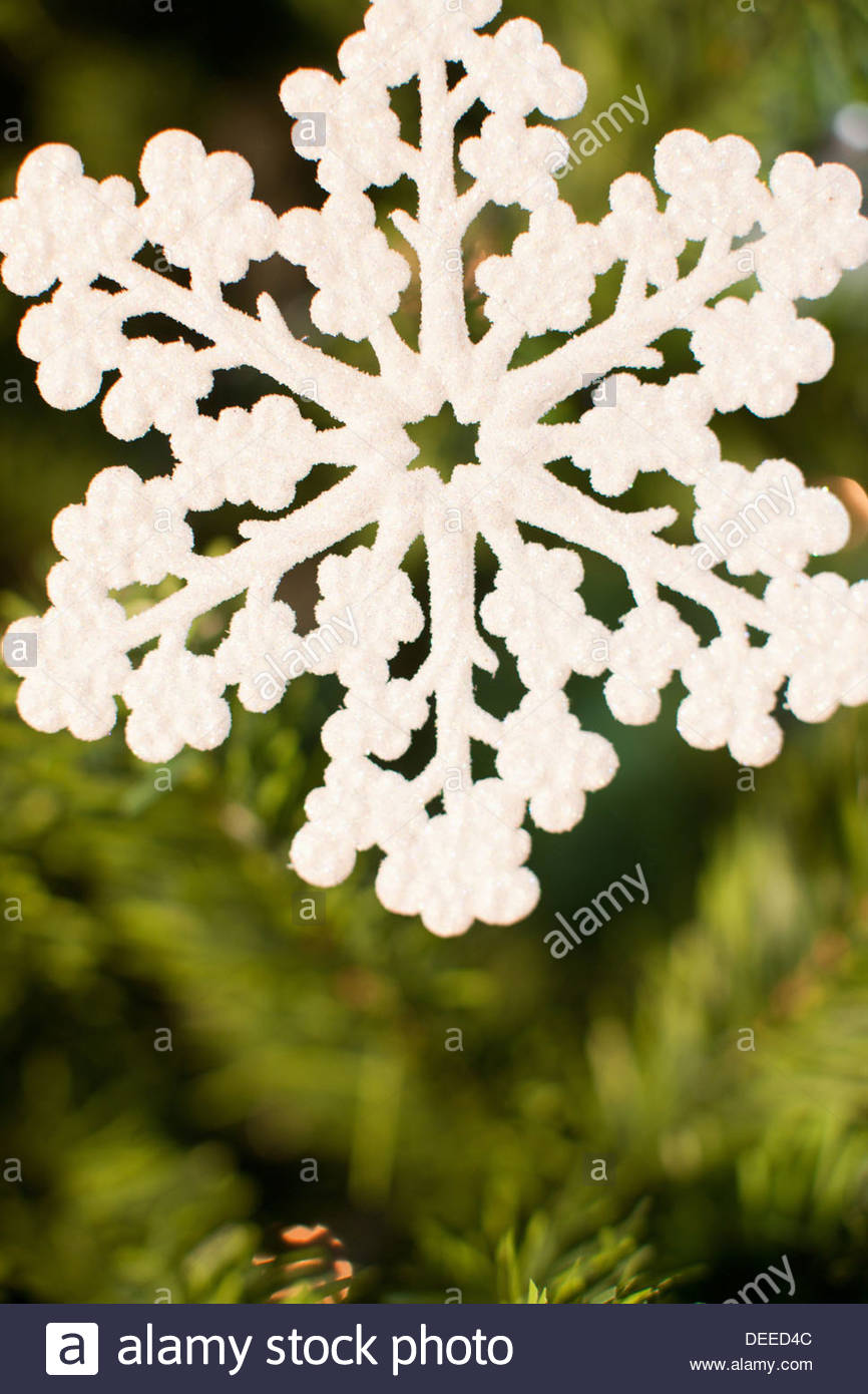Snowflake Christmas ornament on tree - Stock Image