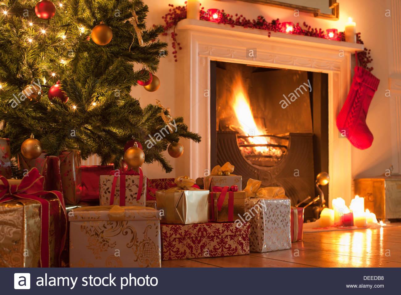 Christmas tree and stocking near fireplace - Stock Image