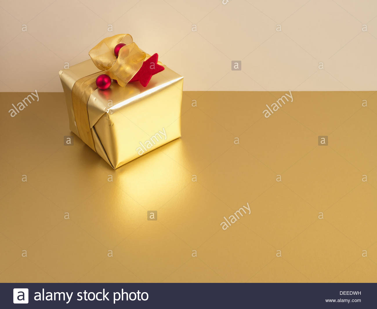 Christmas gift with gold ribbon and gold wrapping - Stock Image