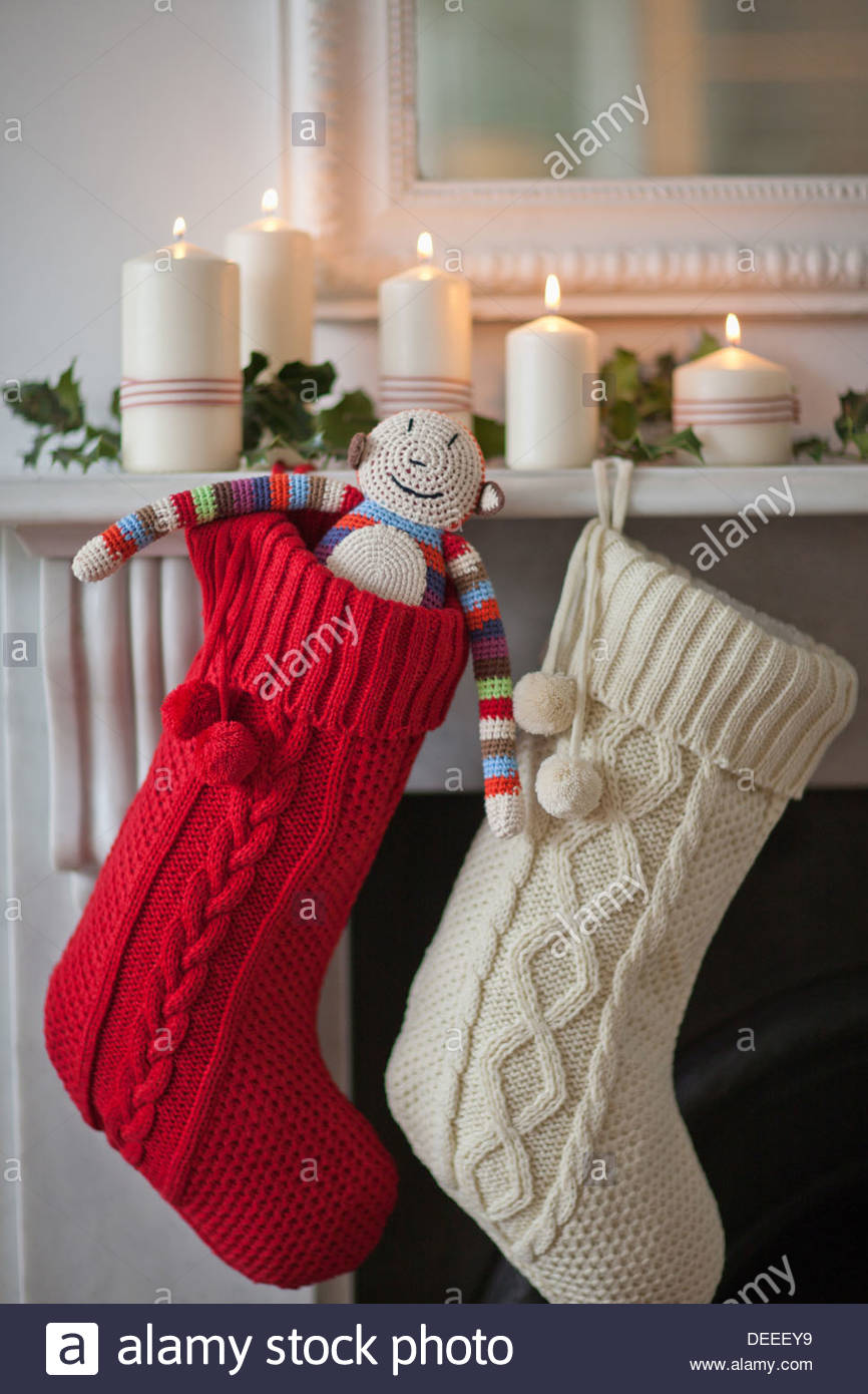 Candles lit on mantelpiece with Christmas stockings - Stock Image