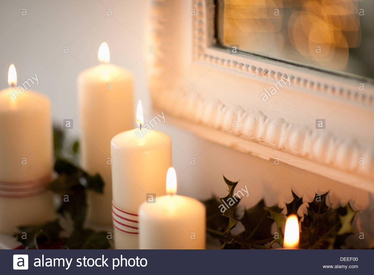 Candles lit on mantelpiece - Stock Image
