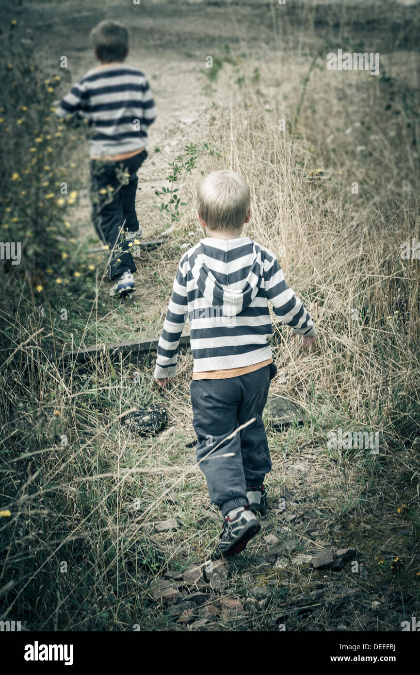 Two boys (4-7) running in meadow, France. - Stock Image