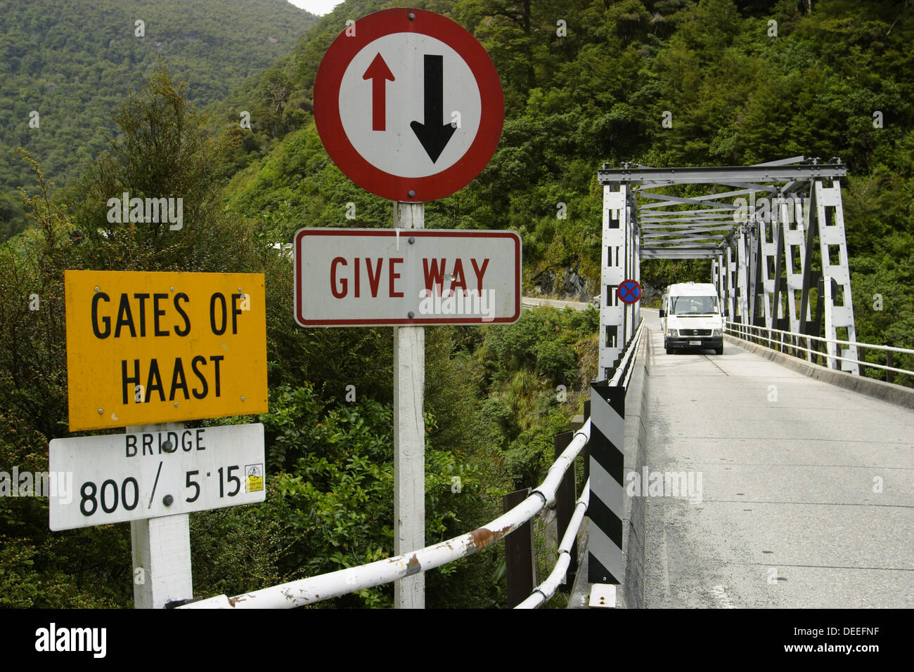 Caravan on one-lane bridge over Gates of Haast, right of way sign, yield. Haast Pass. New Zealand Stock Photo