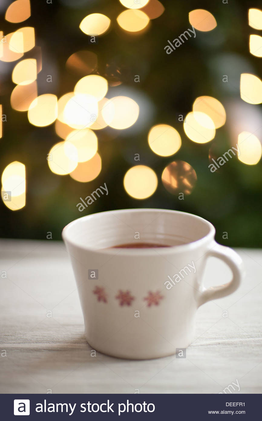 Mug of hot cocoa, Christmas tree in background - Stock Image