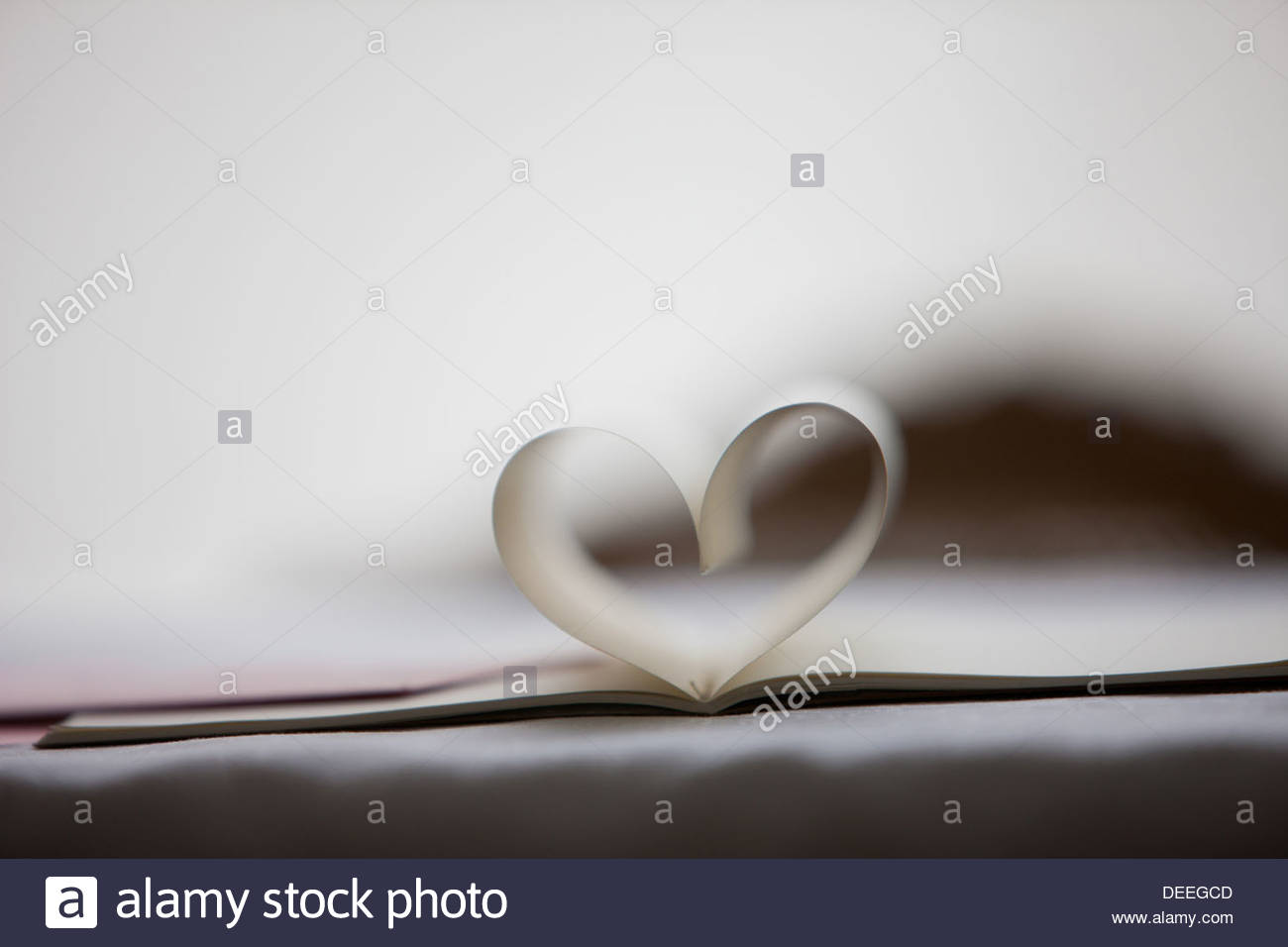 Close up of lipstick kiss on envelope and pages of notebook forming heart-shape - Stock Image