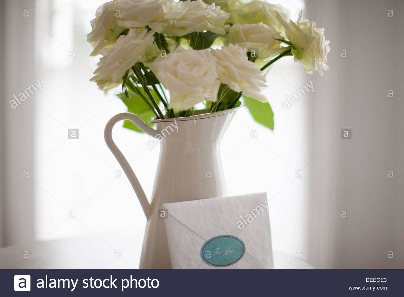 Card leaning against white rose bouquet in pitcher - Stock Image