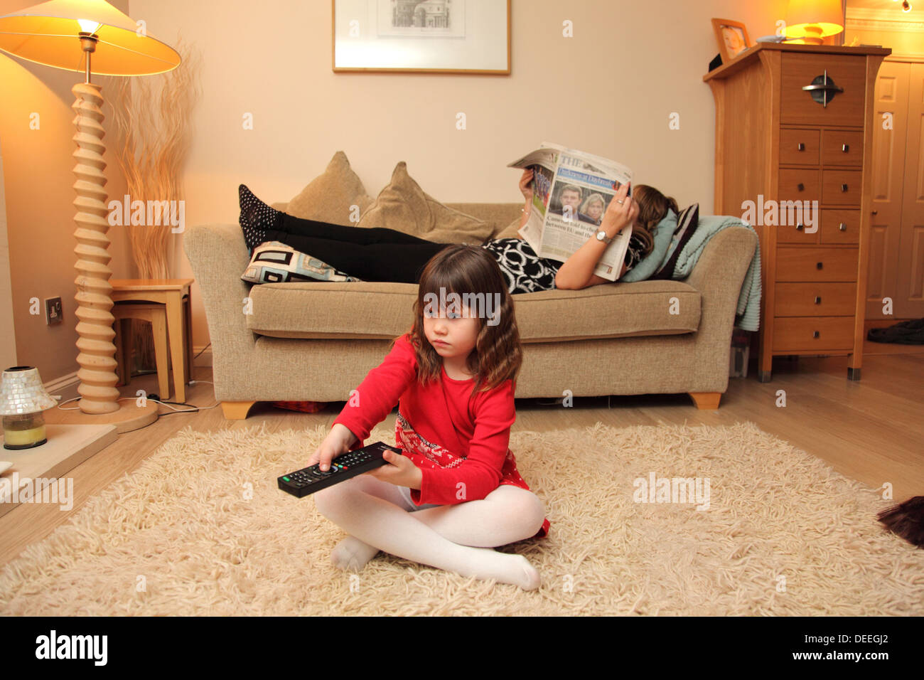 A young girl sits on the floor and operates the television while her mother ignores her, reading the paper whilst lying on a sofa. - Stock Image