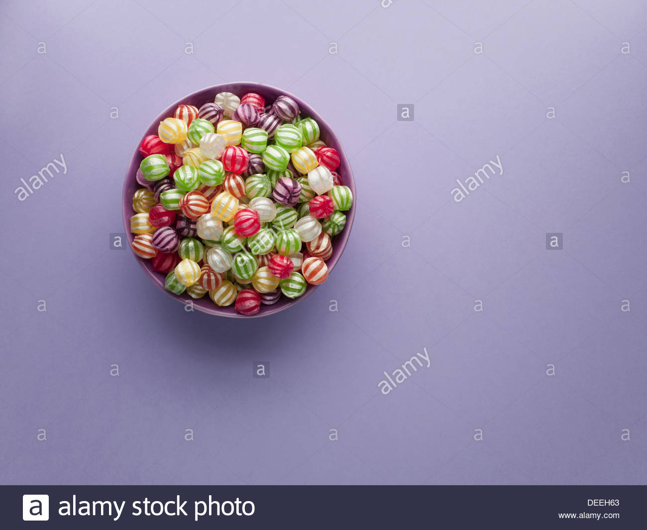Vibrant hard candy in bowl - Stock Image