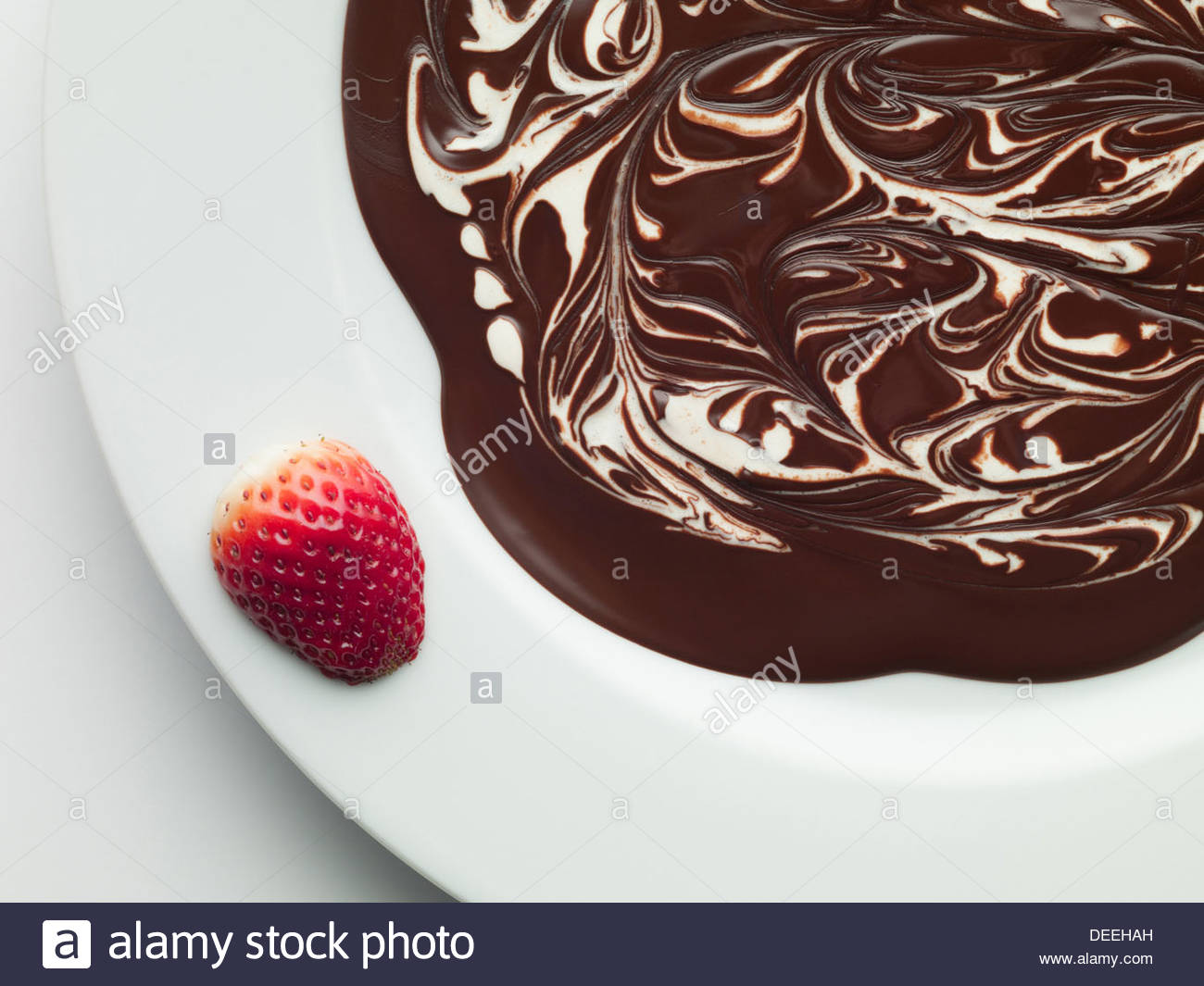 Strawberry on bowl of melted chocolate - Stock Image