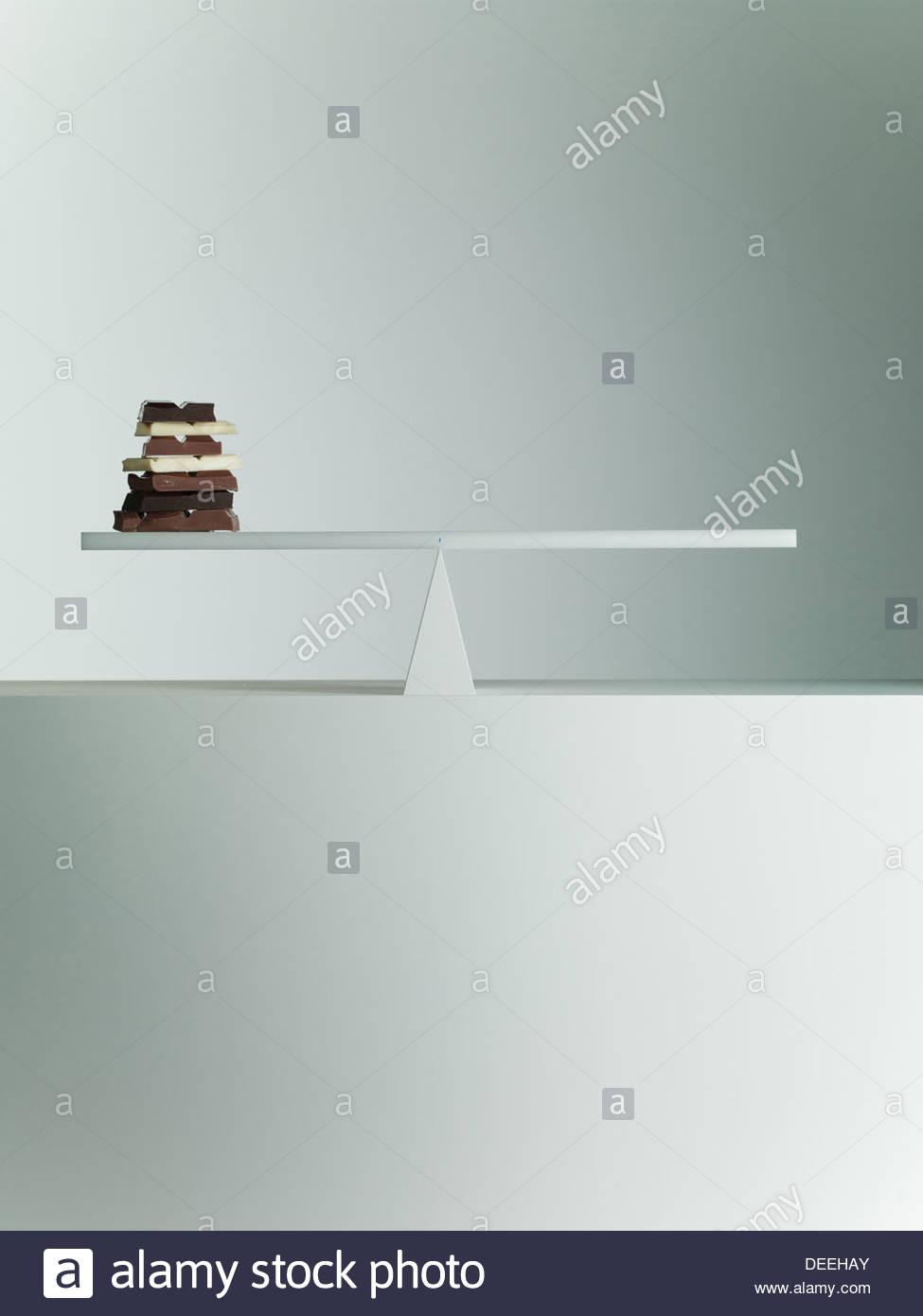 Chocolate bars balanced on seesaw - Stock Image