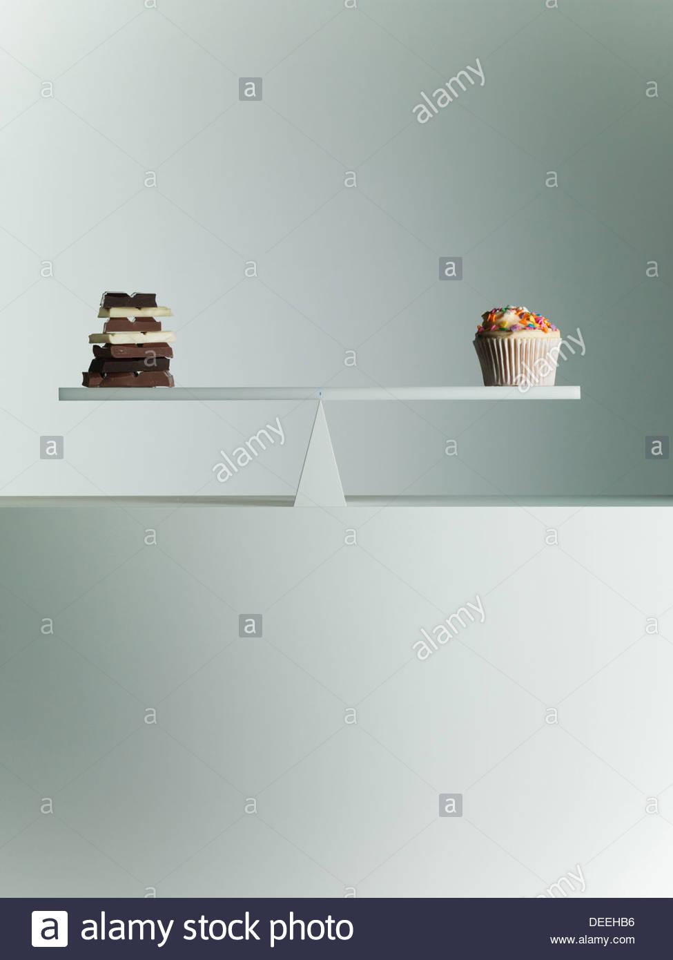 Chocolate bars and Cupcake balanced on seesaw - Stock Image