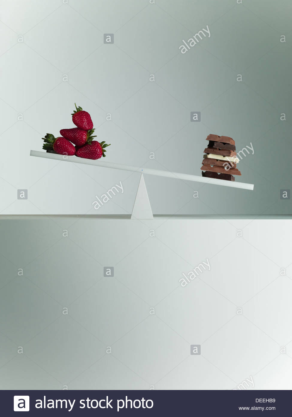 Chocolate bars tipping seesaw with strawberries on opposite end - Stock Image