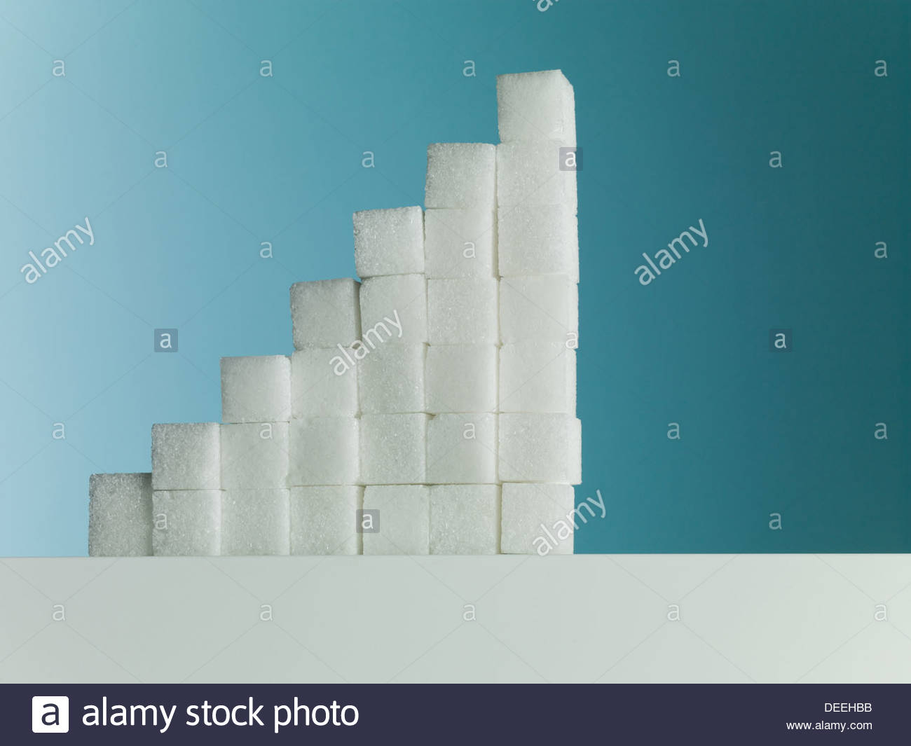 Row of ascending stacks of sugar cubes - Stock Image