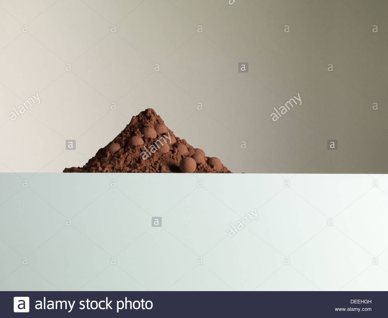 Heap of cocoa powder and truffles - Stock Image