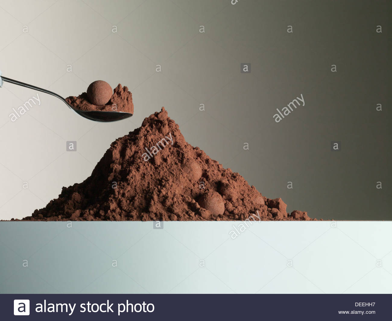 Spoon over heap of cocoa powder - Stock Image