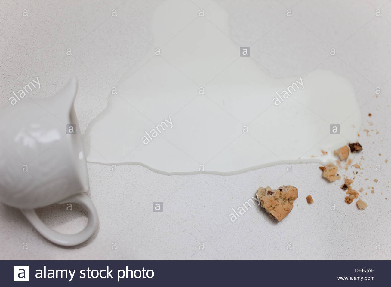 Spilled milk from pitcher and cookie crumbs - Stock Image