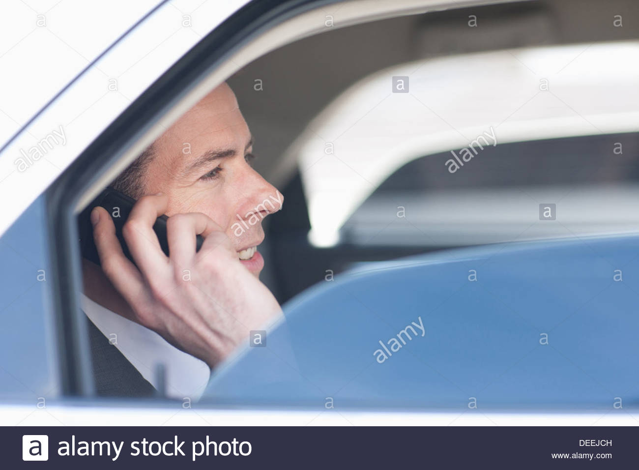 Politician talking on cell phone in backseat Stock Photo