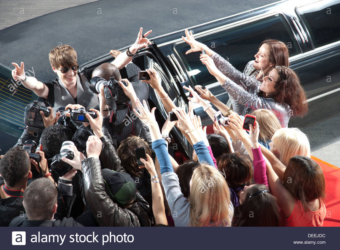 Celebrity emerging from limo towards paparazzi - Stock Image
