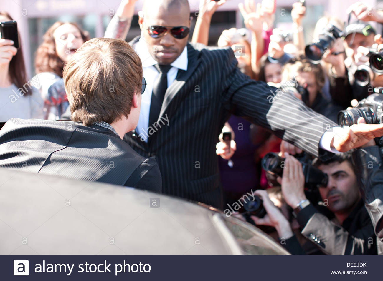 Celebrity emerging from limo toward paparazzi - Stock Image