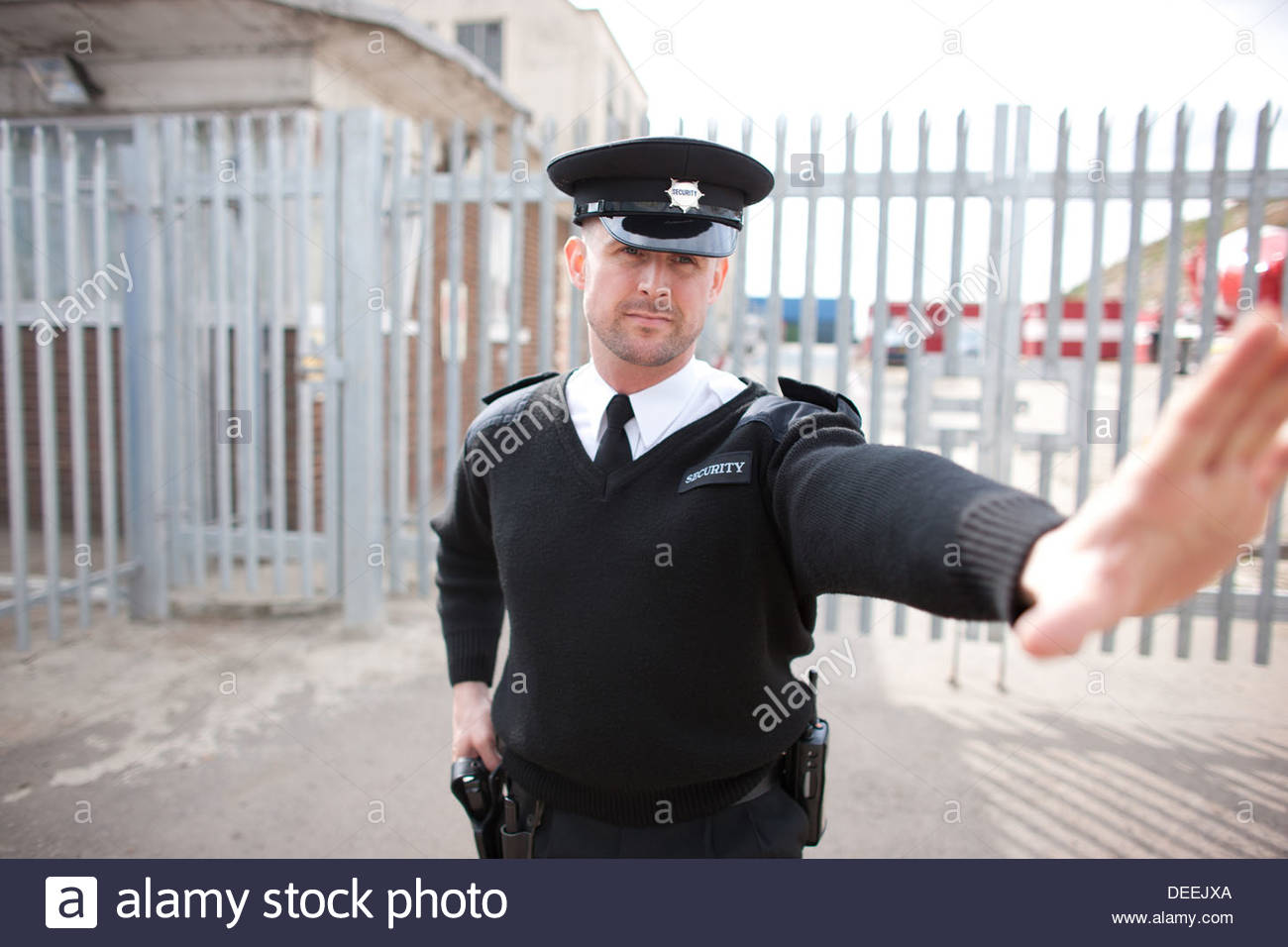 Security guard holding hand out - Stock Image