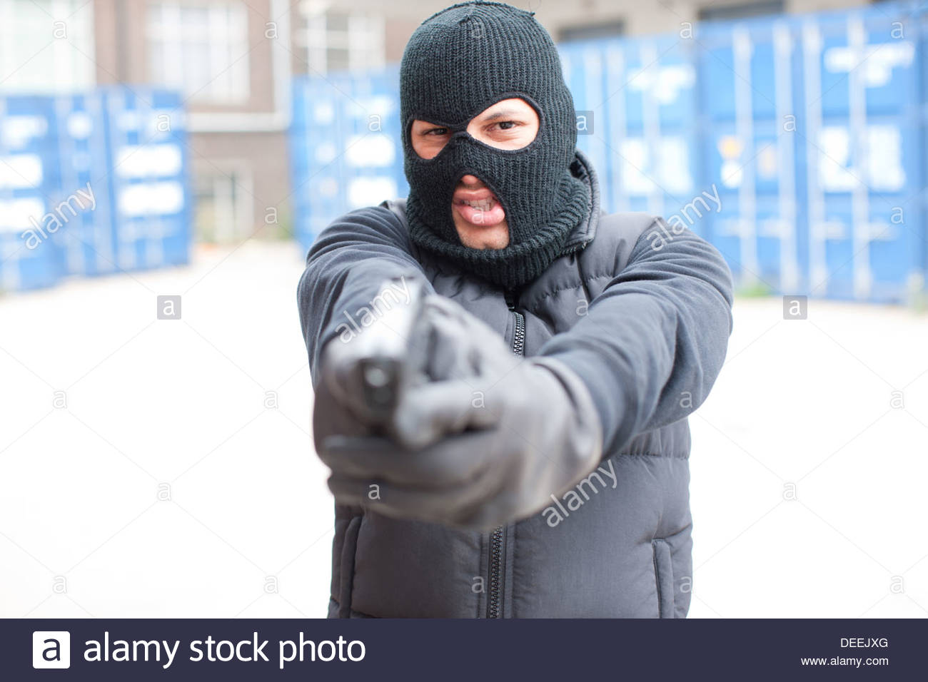 Man in ski mask holding gun Stock Photo