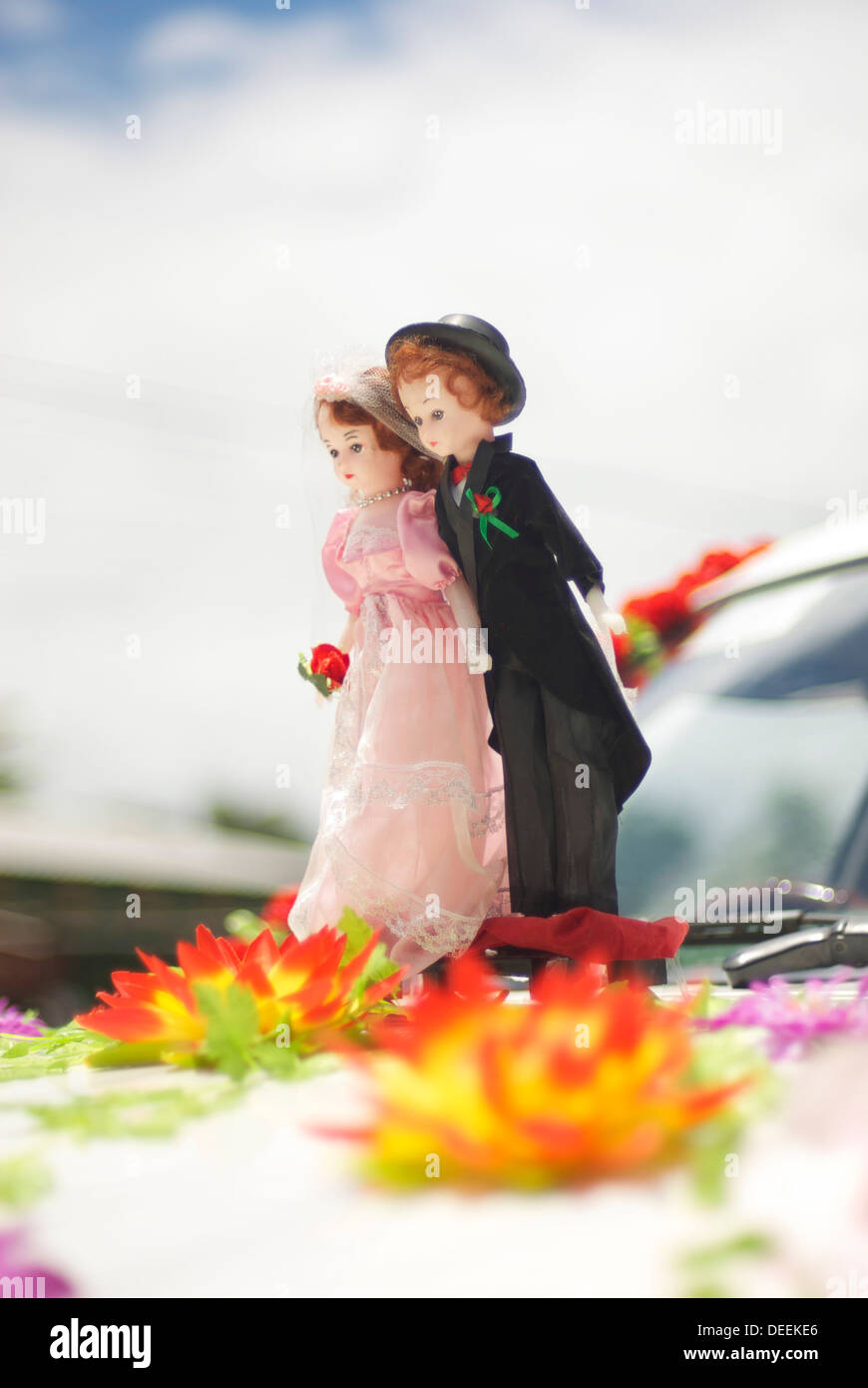 Miniature smart couple based on front car ready for wedding with flowers on their feet Stock Photo