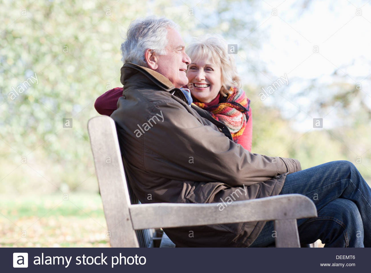 Senior couple hugging in park bench - Stock Image