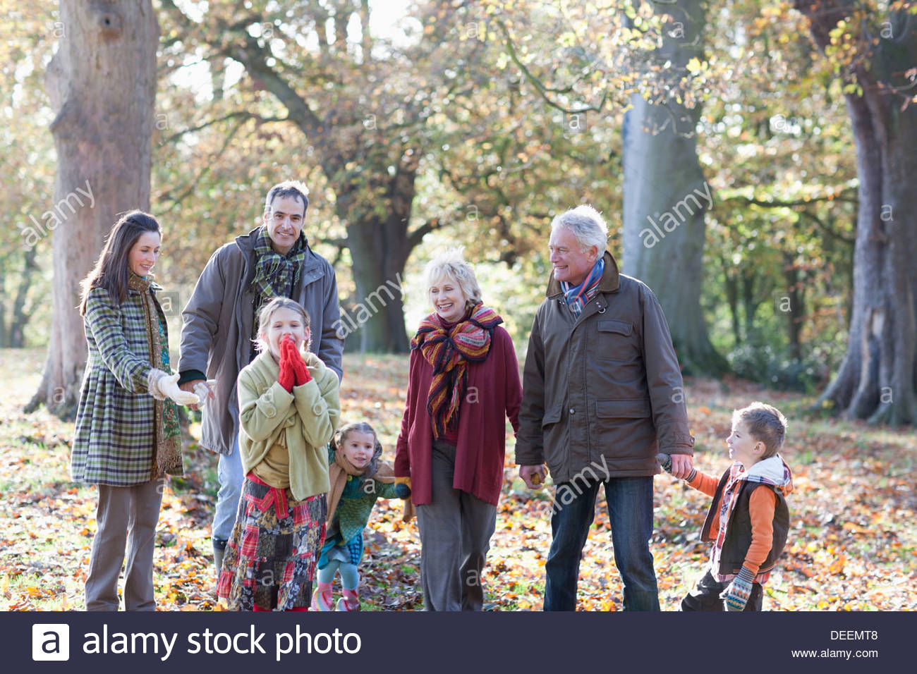 Extended family holding hands and walking in park - Stock Image