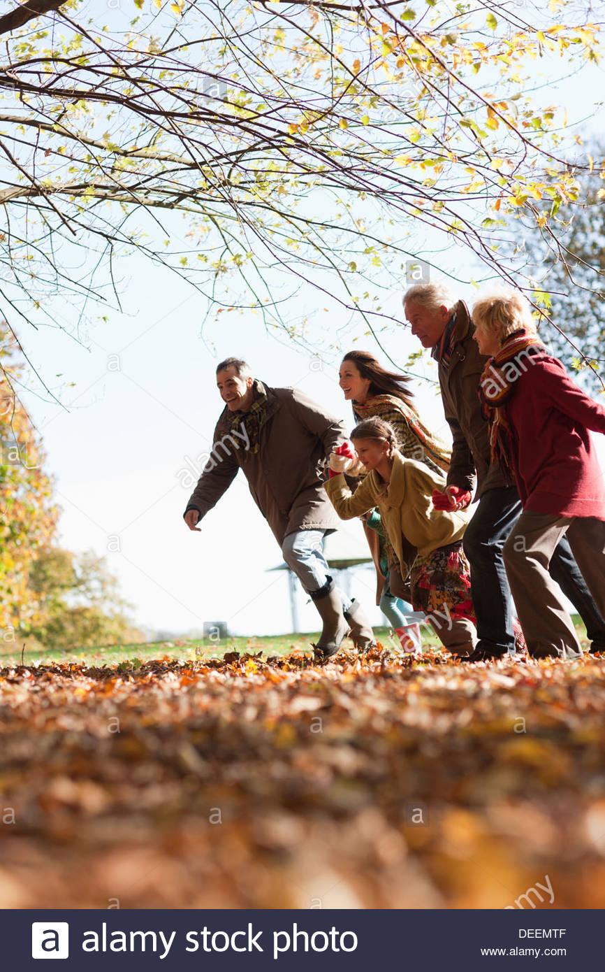 Extended family running in park - Stock Image