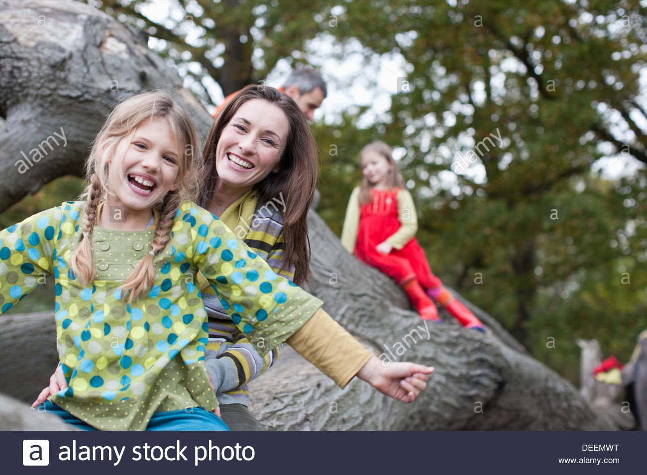 Family climbing on tree branch - Stock Image