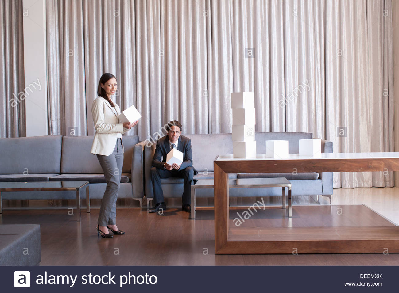 Business people stacking cubes in  hotel lobby - Stock Image