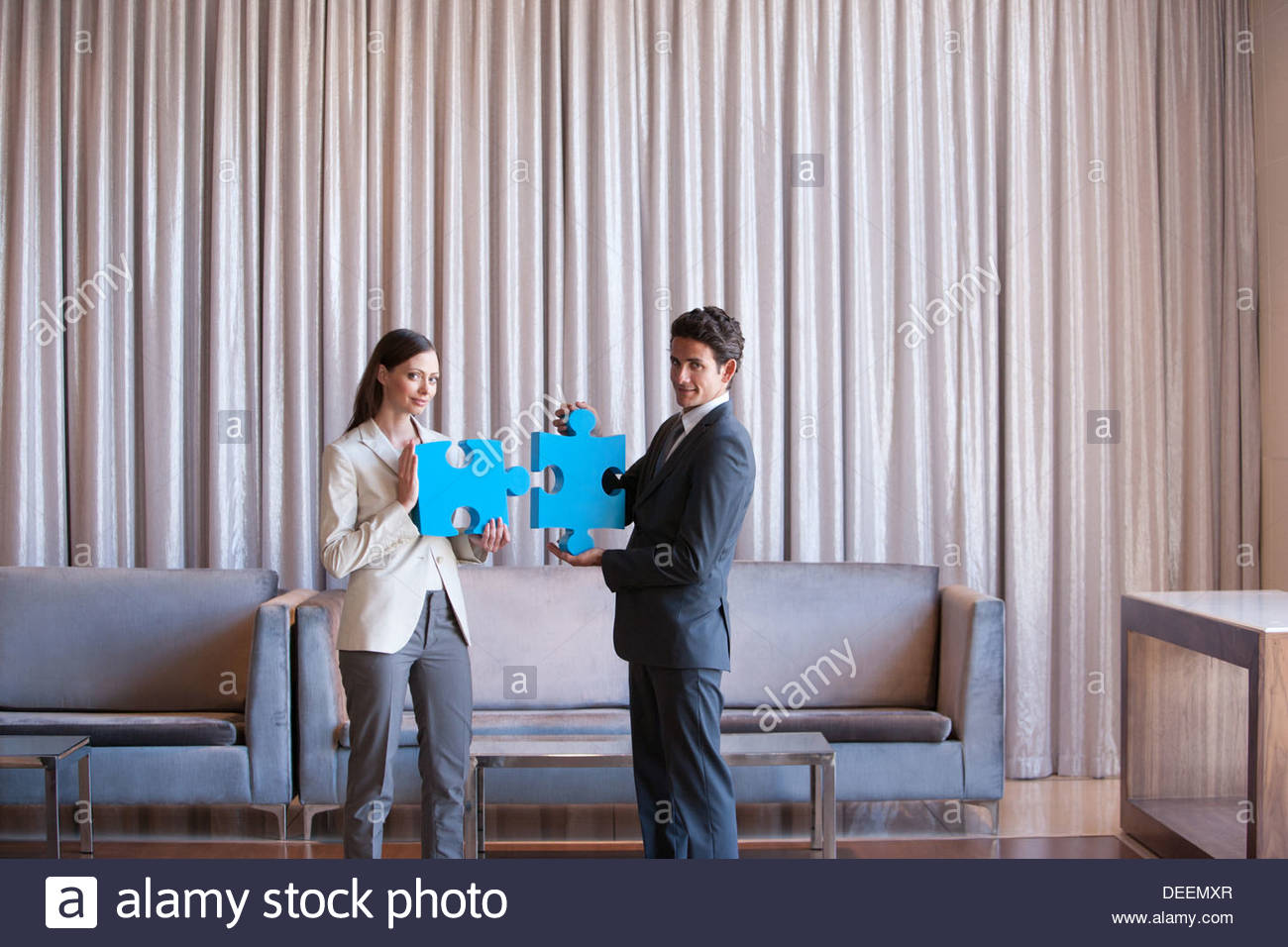 Business people holding jigsaw puzzle pieces in hotel lobby - Stock Image