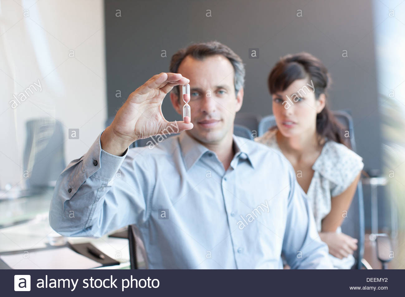 Businessman looking at hourglass in conference room - Stock Image