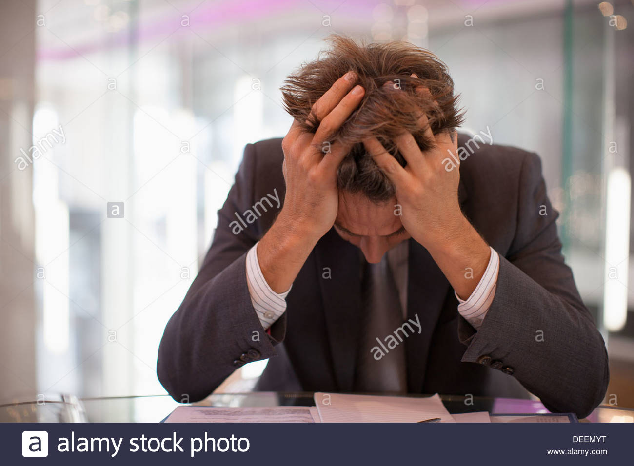 Frustrated businessman sitting at desk with  head in hands - Stock Image