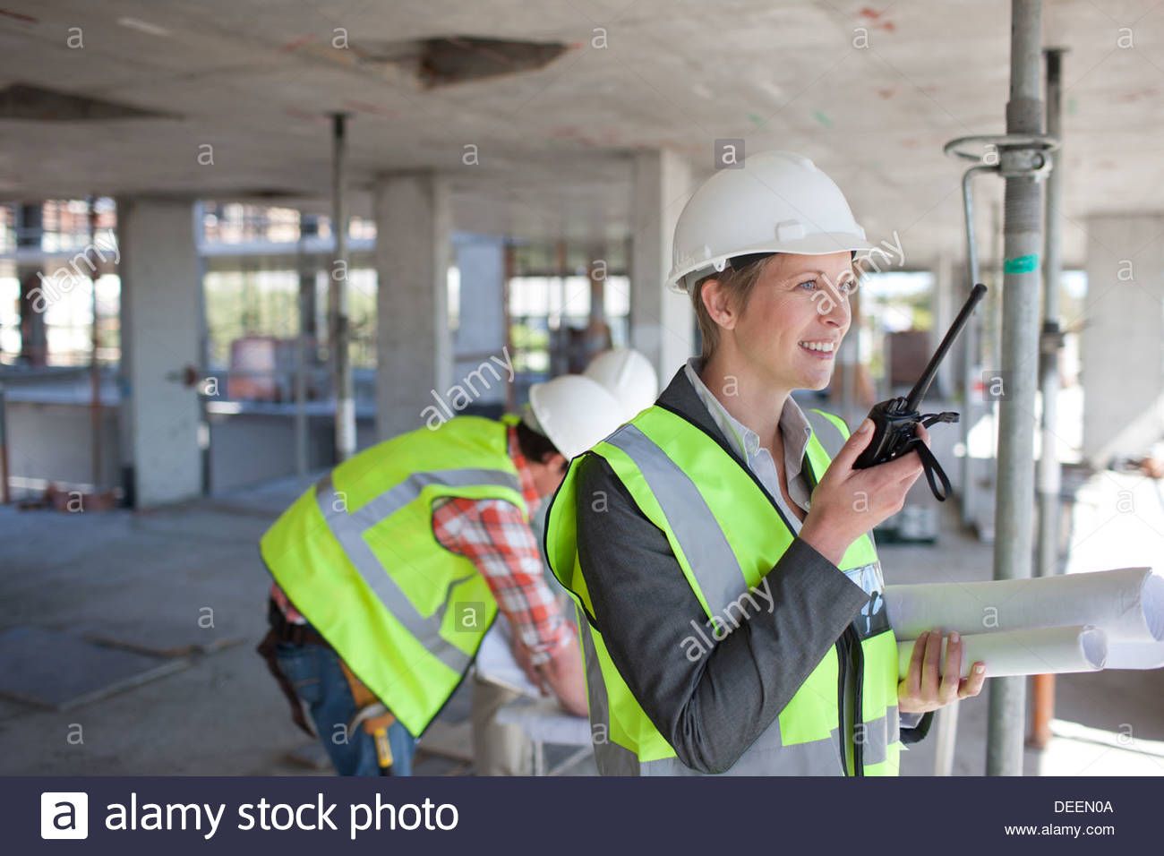Businesswoman talking on walkie talkie on construction site - Stock Image