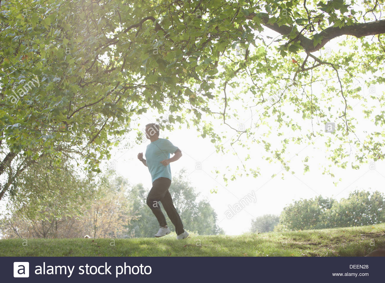 Determined man jogging outdoors - Stock Image