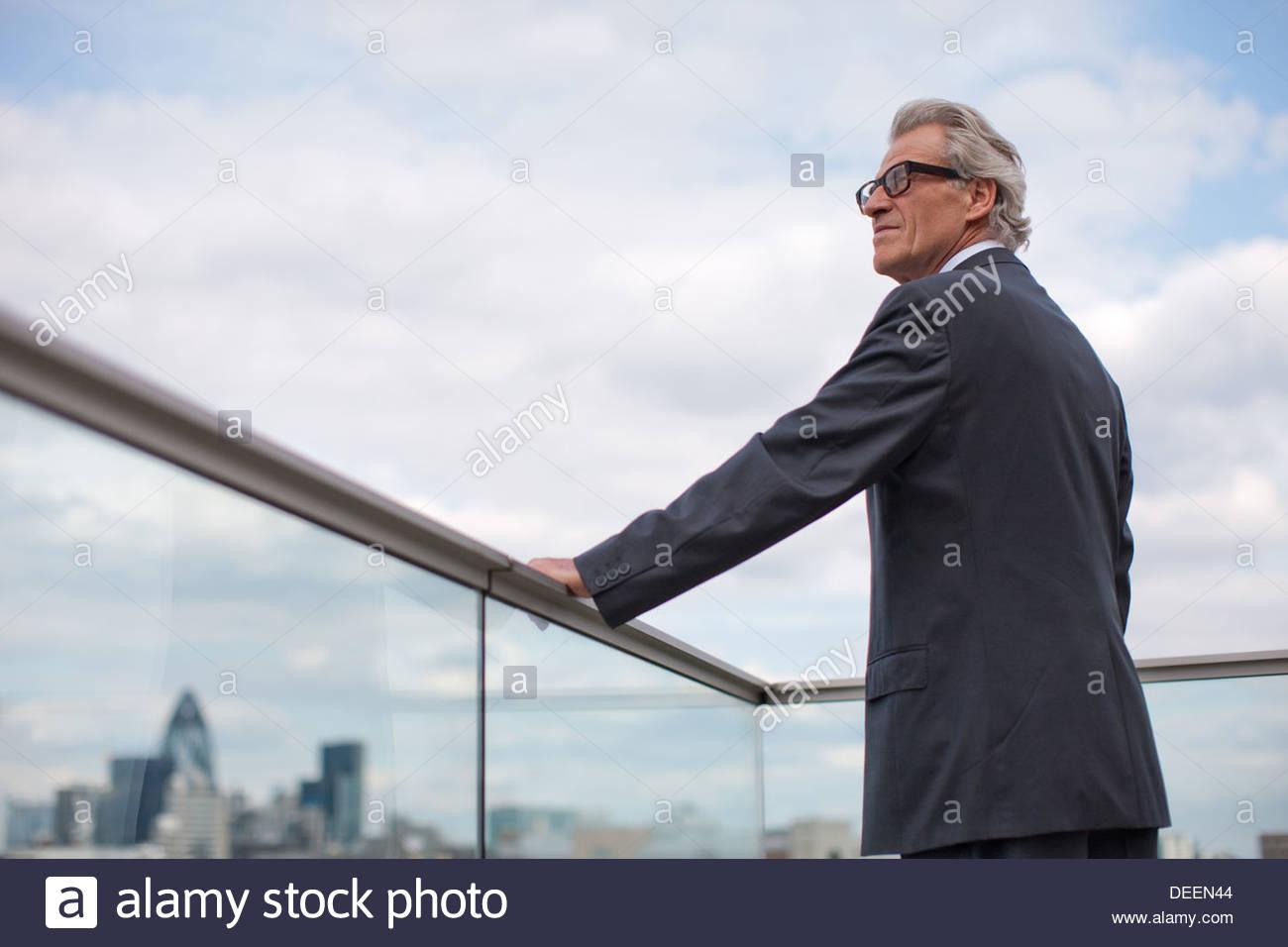 Businessman standing on balcony railing - Stock Image