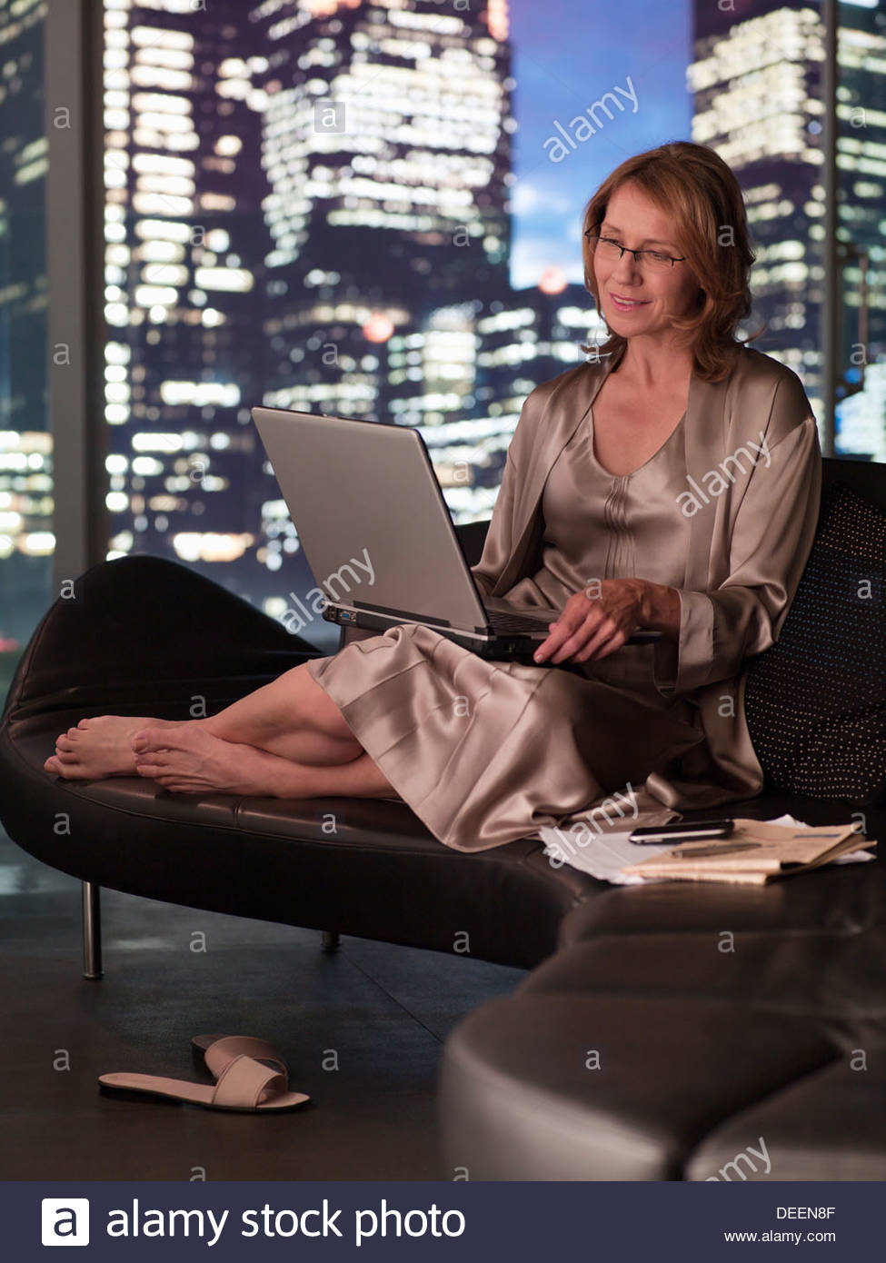 Woman in nightgown using laptop at night Stock Photo