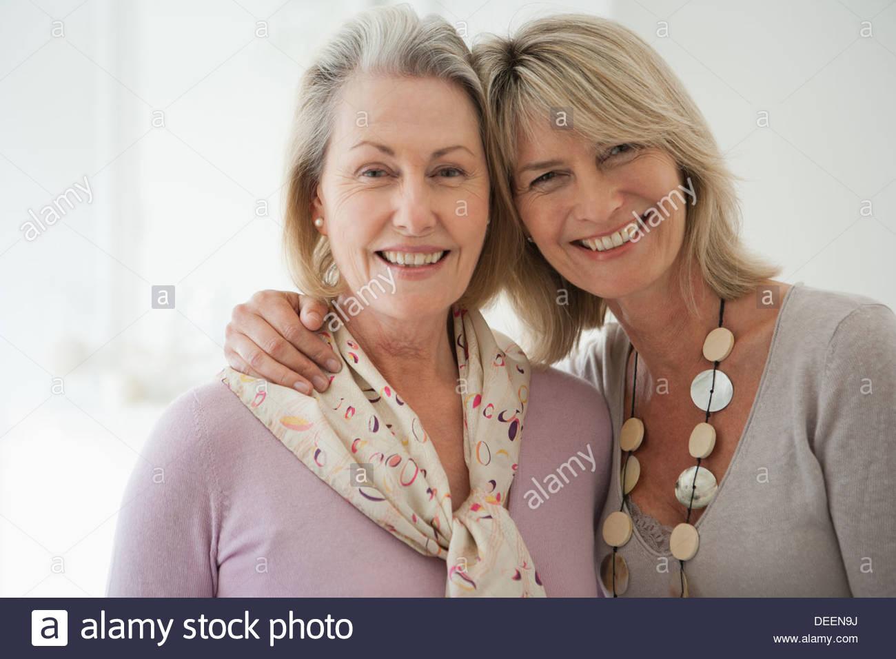 Smiling sisters hugging - Stock Image