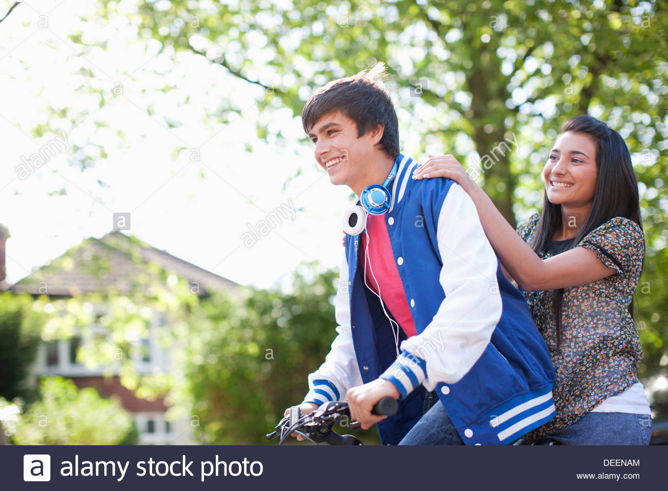Teenage boy riding girlfriend on bicycle - Stock Image