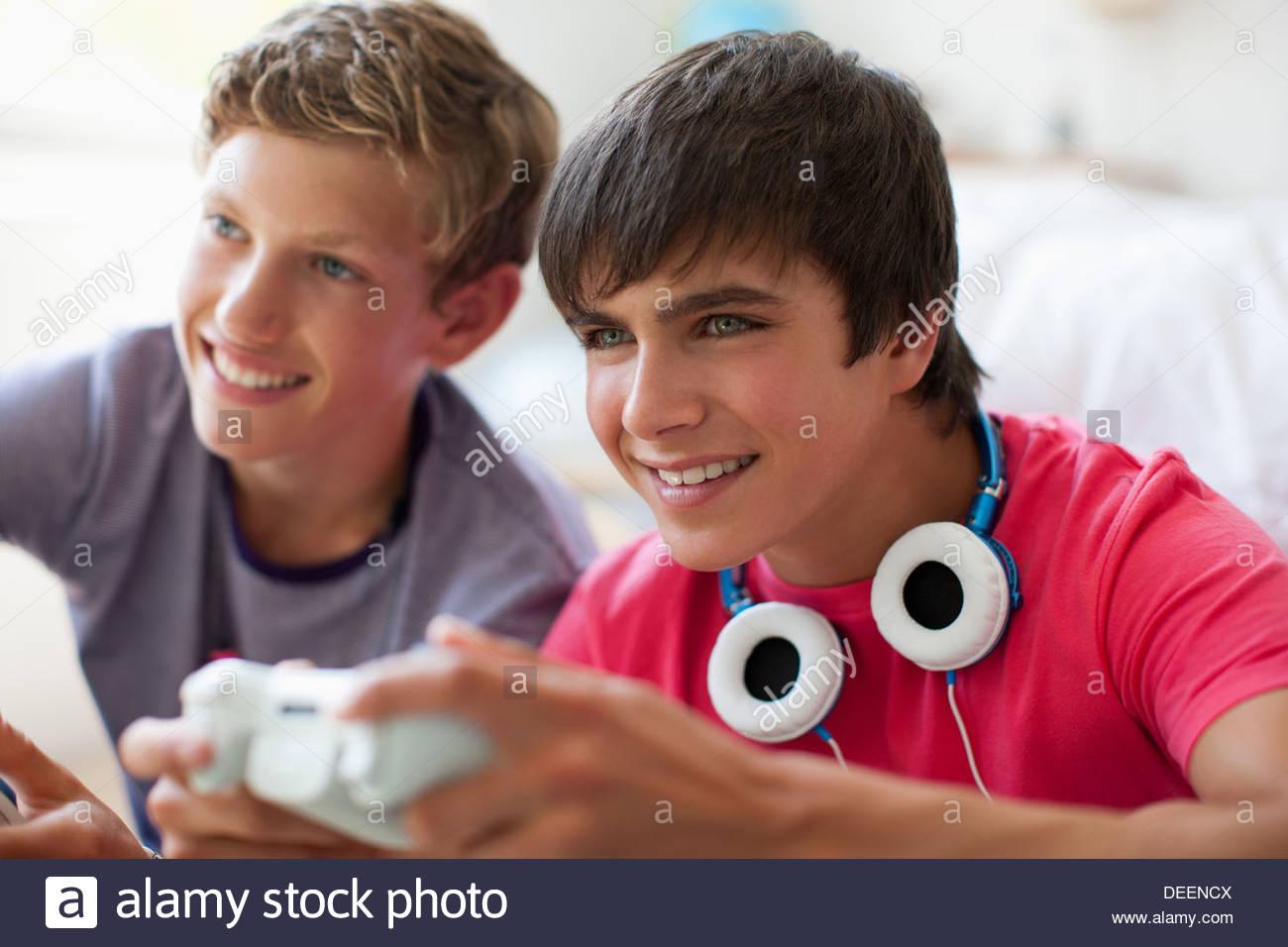 Smiling teenage boys playing video game - Stock Image