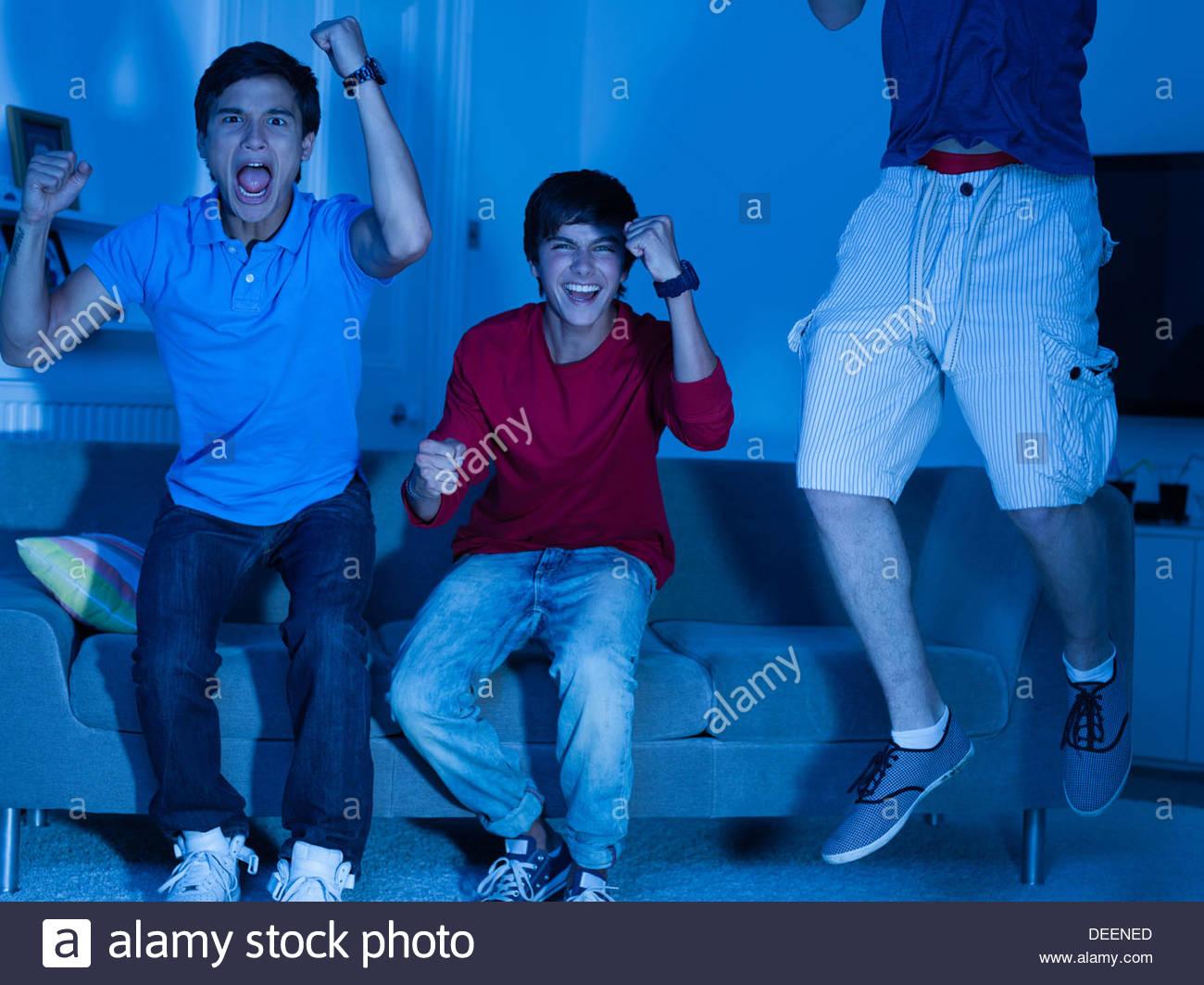 Shouting teenage boys watching television - Stock Image