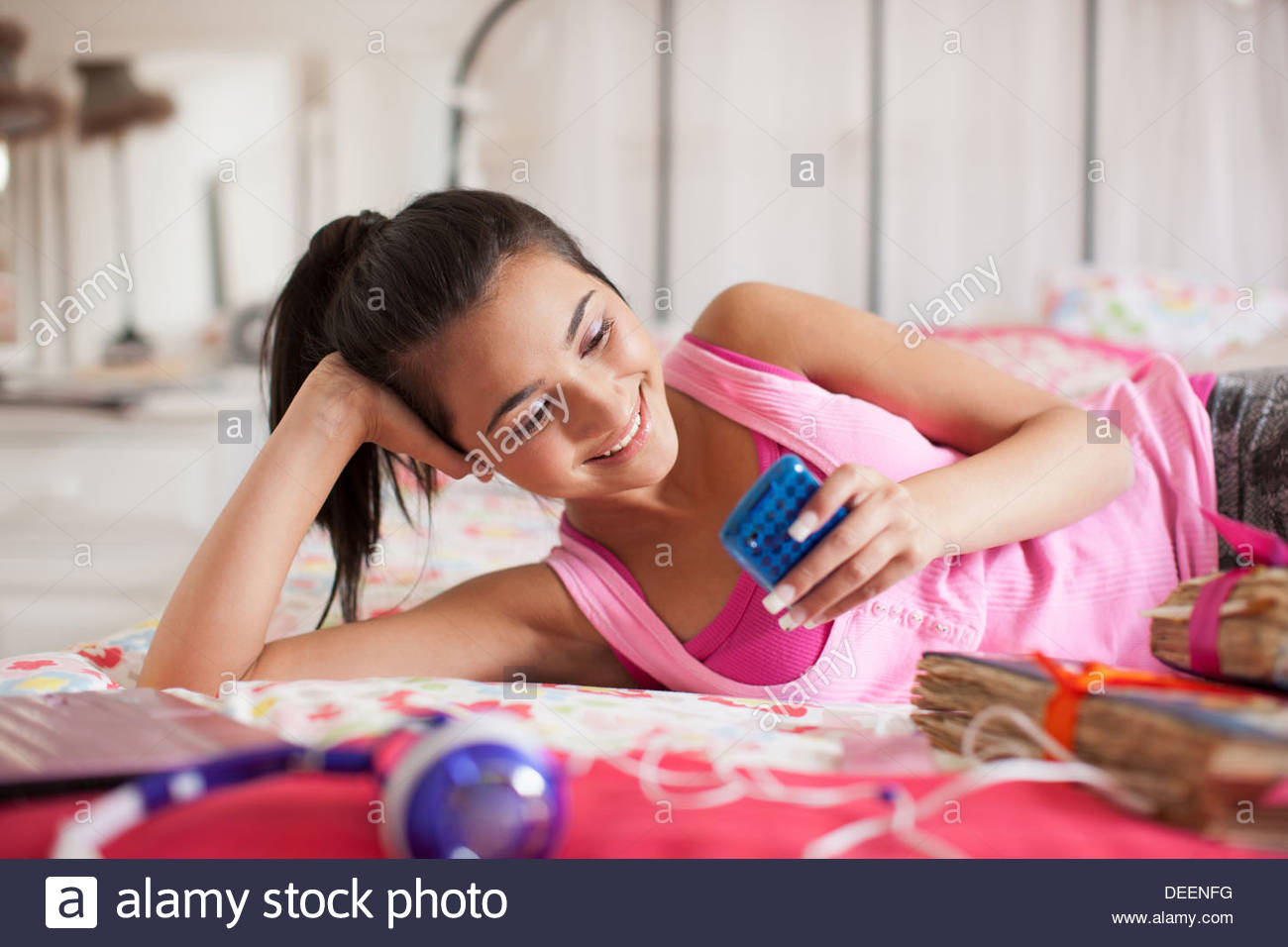 Teenage girl laying on bed text messaging on cell phone - Stock Image