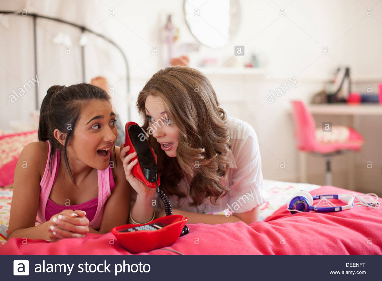 Teenage girls talking on telephone in bedroom - Stock Image