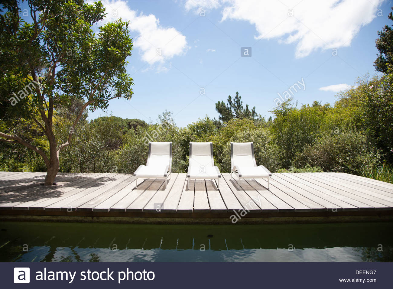 Swimming pool and lounge chairs - Stock Image