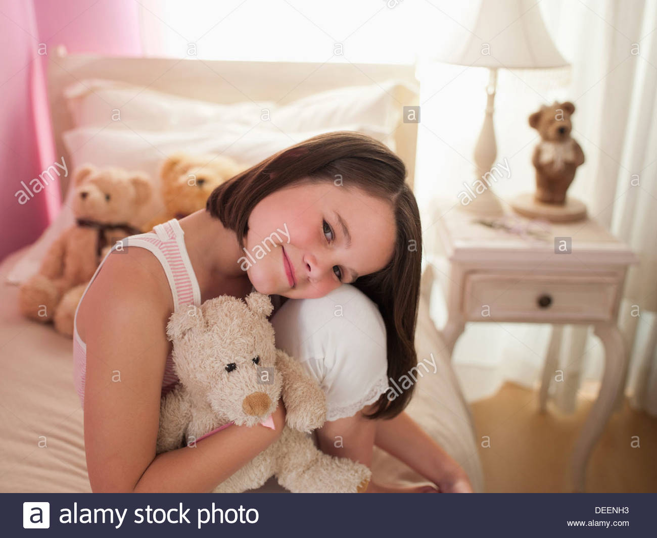 Girl hugging stuffed animal on bed - Stock Image