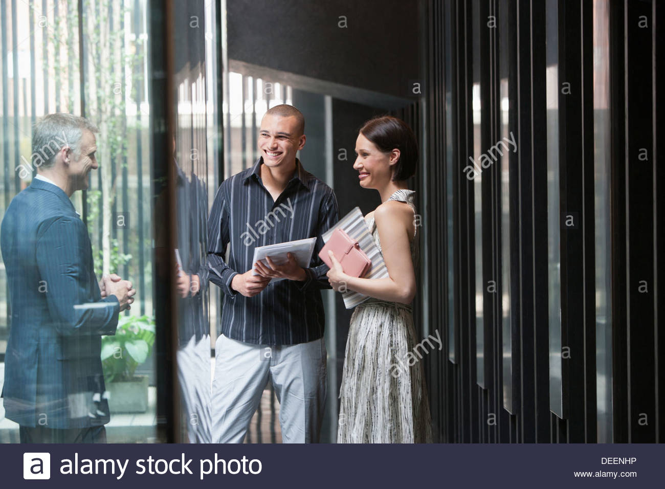Three businesspeople in an office - Stock Image