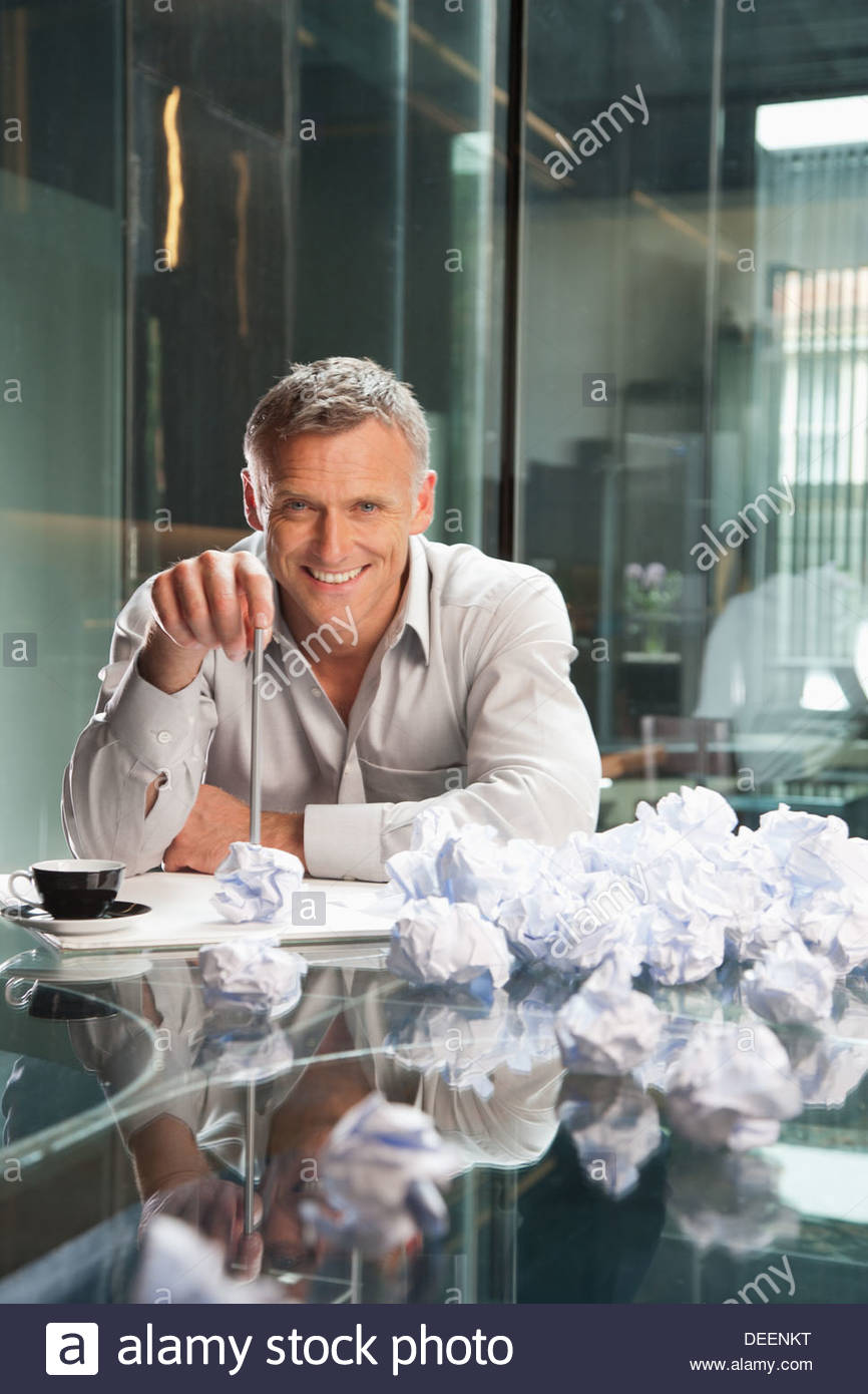 Businessman sitting with crumpled papers in an office - Stock Image